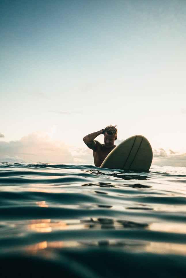 man holding white surfboard